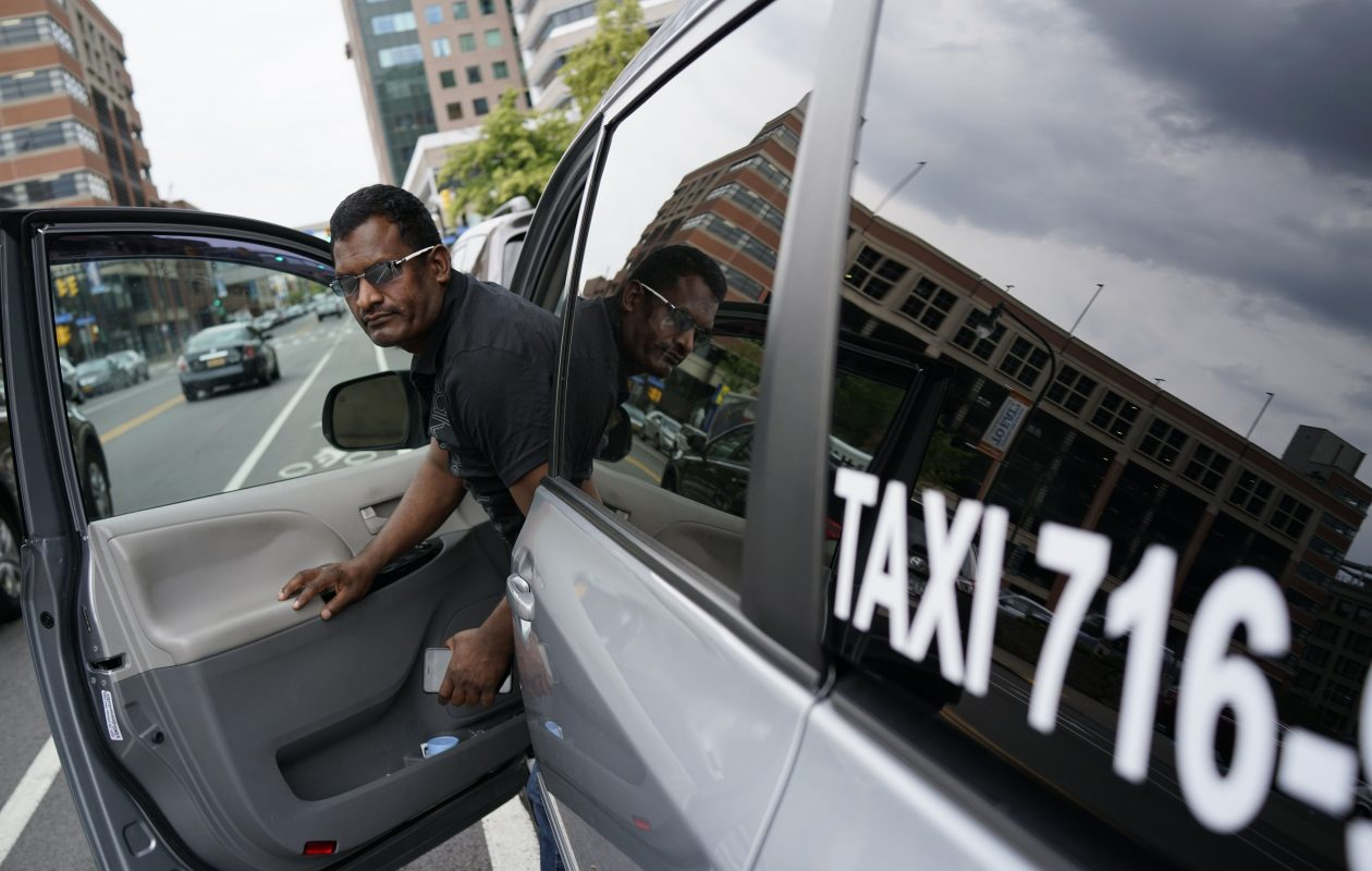Taxi driver Ranjan Appukkuddy steps out of his cab while waiting for a fare on Pearl Street outside the Hyatt Regency Buffalo on Thursday. Last Thursday he had more than 10 fares, but with ride hailing services like Uber and Lyft beginning today, he had only two in the six hours he had worked.  (Derek Gee/Buffalo News)