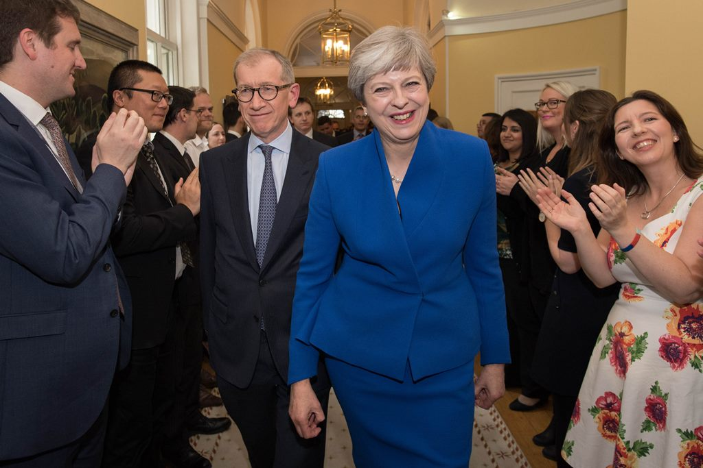 British Prime Minister Theresa May and her husband Philip are clapped into 10 Downing Street in by staff Friday after returning from seeing Queen Elizabeth II at Buckingham Palace.  (Getty Images)