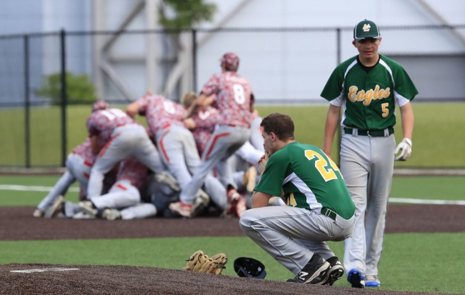North Collins pitcher Brandon Zielinski crouches on the mound as Fort Ann celebrates its 5-4 walk-off win in the Class D championship. (Harry Scull Jr./The Buffalo News)