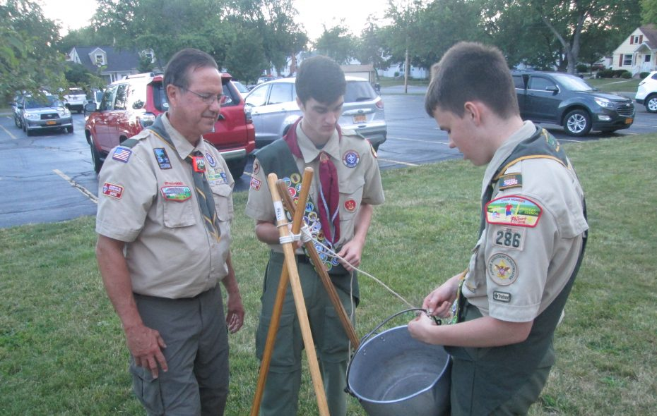 Boy Scout Troop 286 Scoutmaster Mark Oetinger and Scouts Jimmy Dahlke and Josh Korman stand around a cooking triped at a scouting event. (Photo by Ken Kuschke)