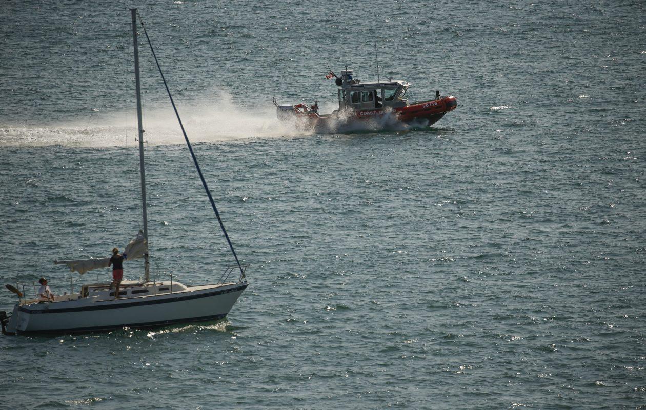 A U.S. Coast Guard vessel passes a sailboat. (Derek Gee/Buffalo News)