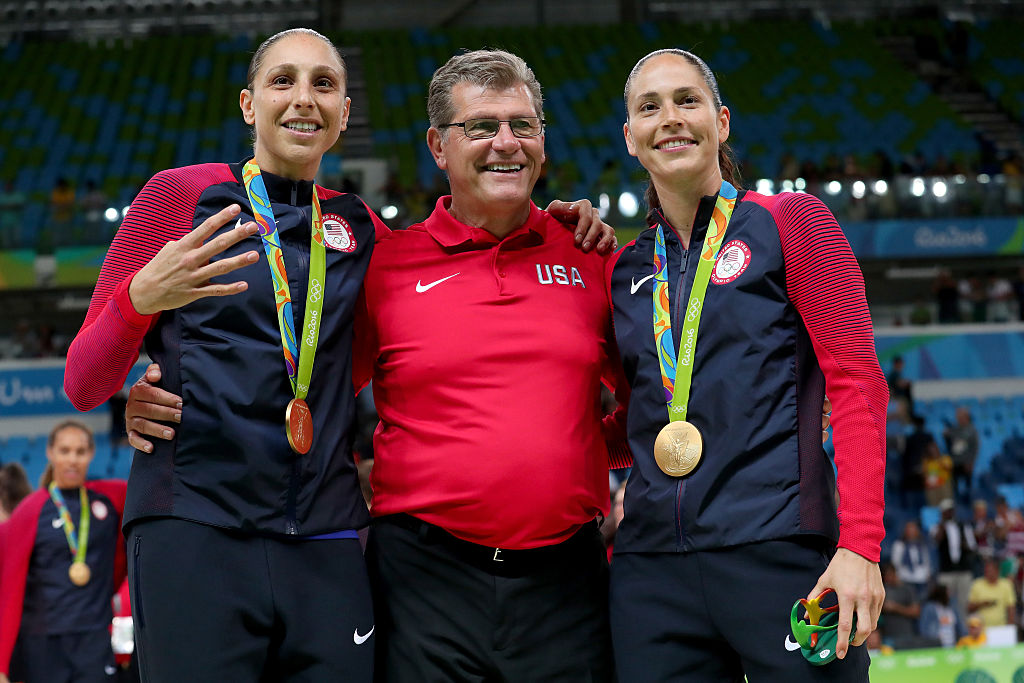 Diana Taurasi (left), USA coach Geno Auriemma and Sue Bird celebrate their gold medal at the 2016 Rio Olympics. Taurasi is holding up four fingers for her fourth straight gold with Team USA. (Getty Images)