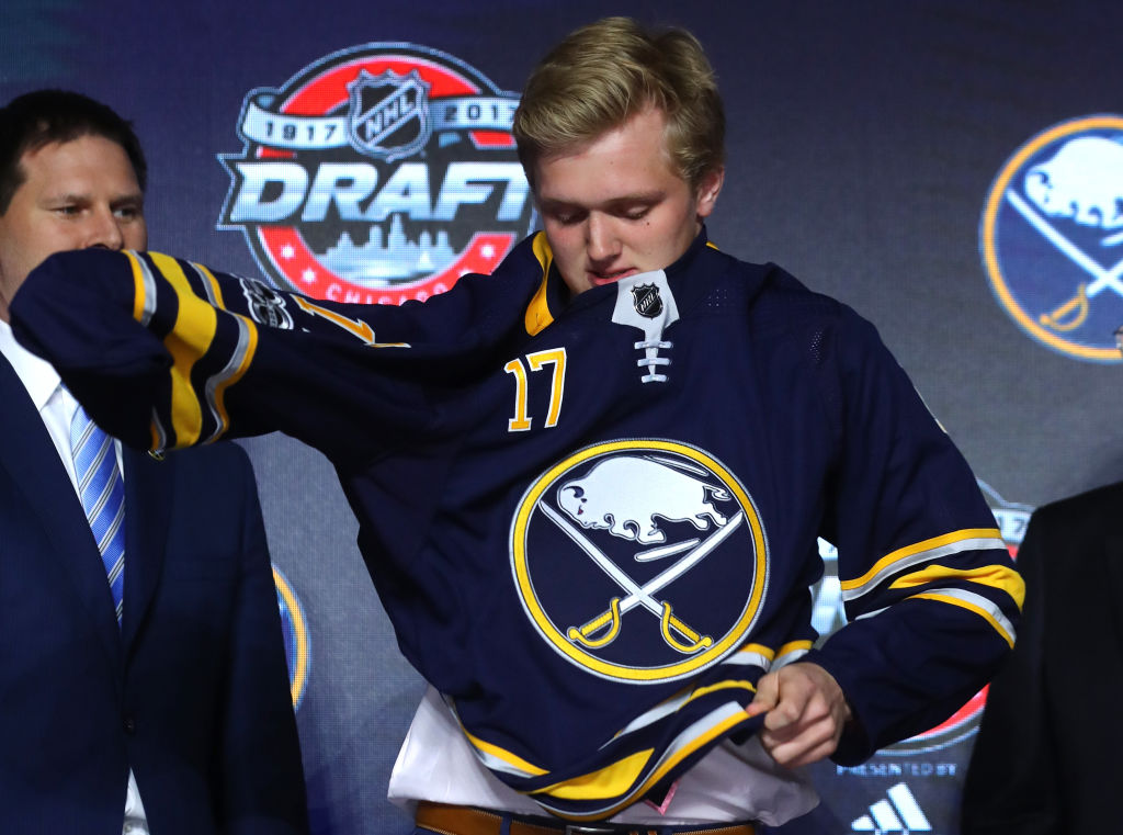 Casey Mittelstadt puts on the Buffalo Sabres jersey after being selected eighth overall during the 2017 NHL Draft at the United Center on June 23, 2017 in Chicago. (Getty Images)