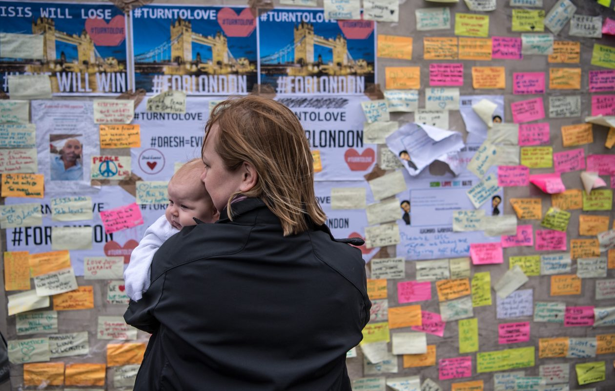 A woman holds her baby as she views messages of support and condolence on London Bridge following last weekend's terror attack. (Getty Images)