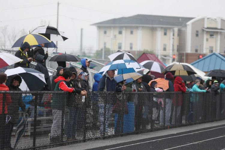 Fans try to stay dry in the pouring rain May 6 during the Adpro Sports Panthers Track & Field Invitational at Sweet Home high school in Amherst. (James P. McCoy/Buffalo News)
