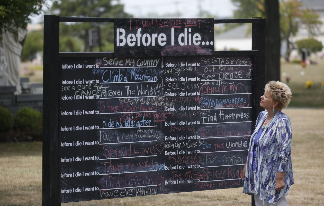 Nancy Weil, former director of grief support with the Buffalo Diocese, has become a 'soul ambassador with Opus Peace, a nonprofit which provides programs to help address grief and guilt that occur during trauma, abuse and self-neglect. Weil is standing in front of a 'Before I die' chalk board  at Mount Olivet Cemetery in the Town of Tonawanda, which she helped bring to the cemetery last year.  (Robert Kirkham/Buffalo News file photo)