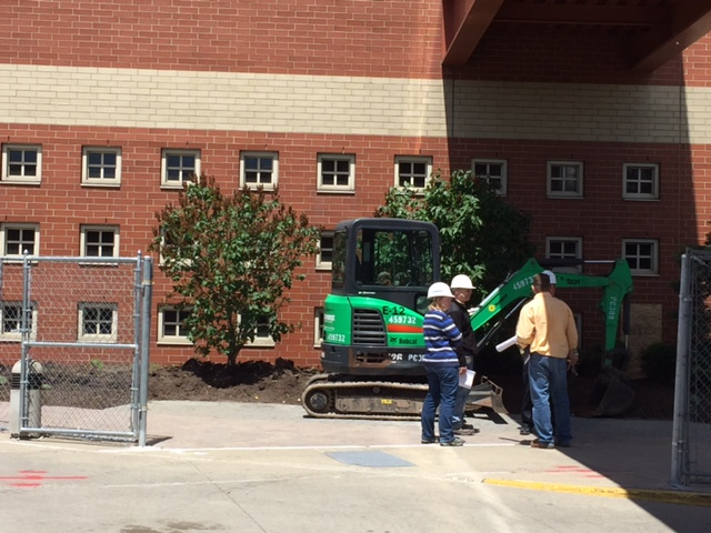 Workers outside Roswell's main building Wednesday where summer work is planned. (Karen Robinson/Buffalo News)