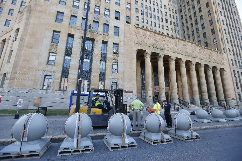 Public works crews Wednesday evening begin installing concrete bollards around the perimeter of City Hall to protect the landmark housing government offices from vehicles that might crash into it – either accidentally or intentionally. (Mark Mullville/Buffalo News)