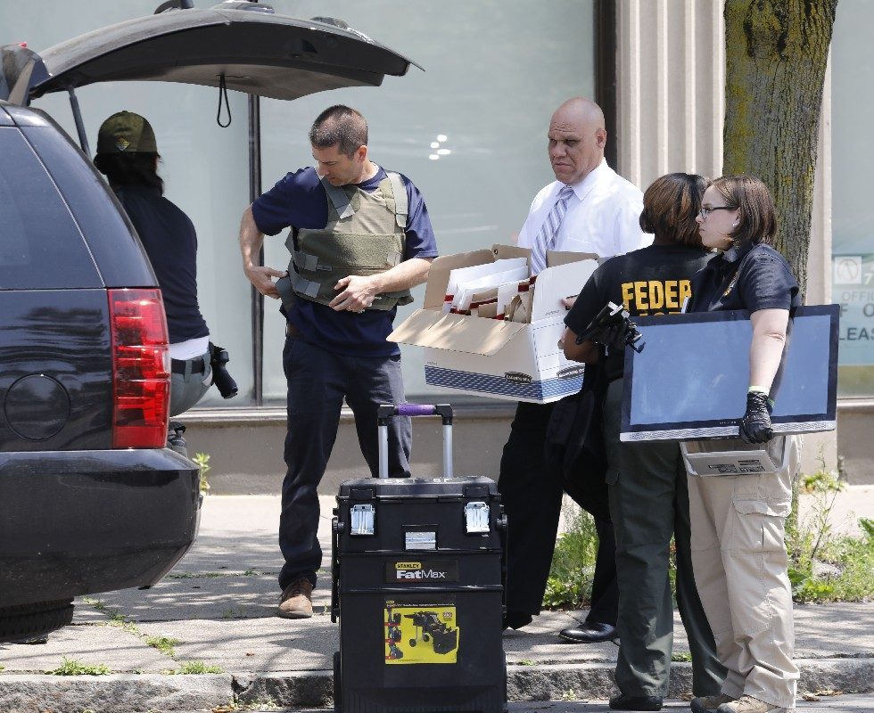 Federal agents emerge from 1325 Main St. in Buffalo on Thursday carrying computers and boxes after executing a search warrant. (Derek Gee/Buffalo News)