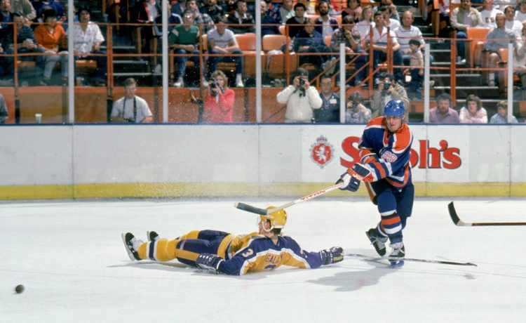 Wayne Gretzky #99 of the Edmonton Oilers makes a pass between defensemen Garry Galley #3 and Jay Wells #24 of the Los Angeles Kings circa March 1988 during a game at the Great Western Forum in Inglewood, California. (Photo by Rick Stewart/Getty Images)