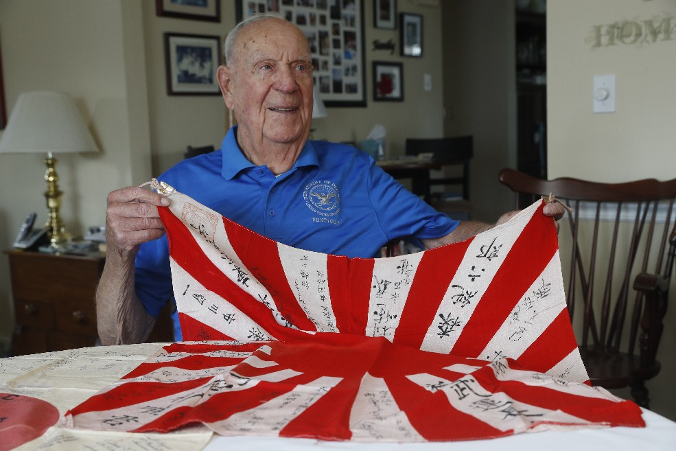 WWII Marine Paul R. Hulub displays flags he obtained while fighting in Japan, where he witnessed civilians jumping off cliffs because of a mistaken fear of what the Americans would do to them.  (John Hickey/Buffalo News)