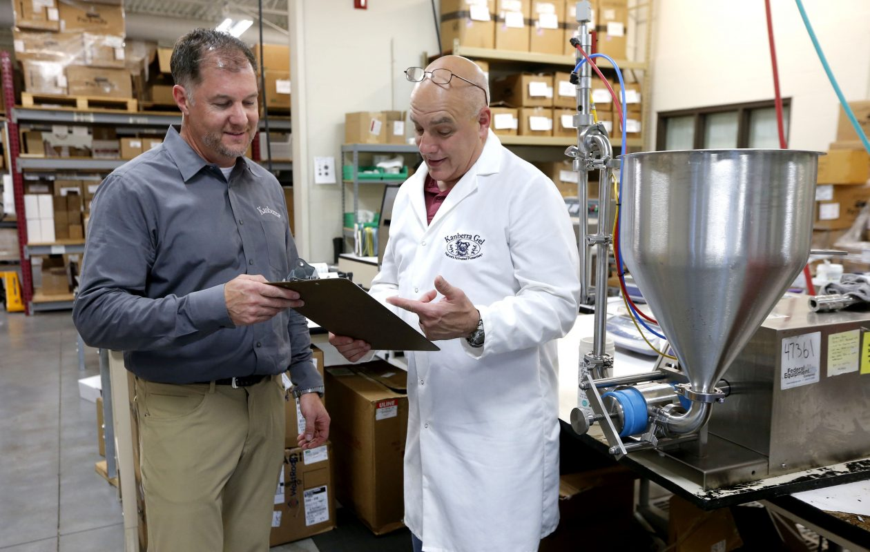 """We're not Sahlen's, or Weber's mustard today, but we're a unique brand that's worldwide."" Joel Solly, president and CEO, left, and Steven Toorongian, right, who heads up the research and development team, discuss results of a new product formulation at Indoor Air Professionals/Kanberra Group in Lancaster. (Robert Kirkham/Buffalo News)"