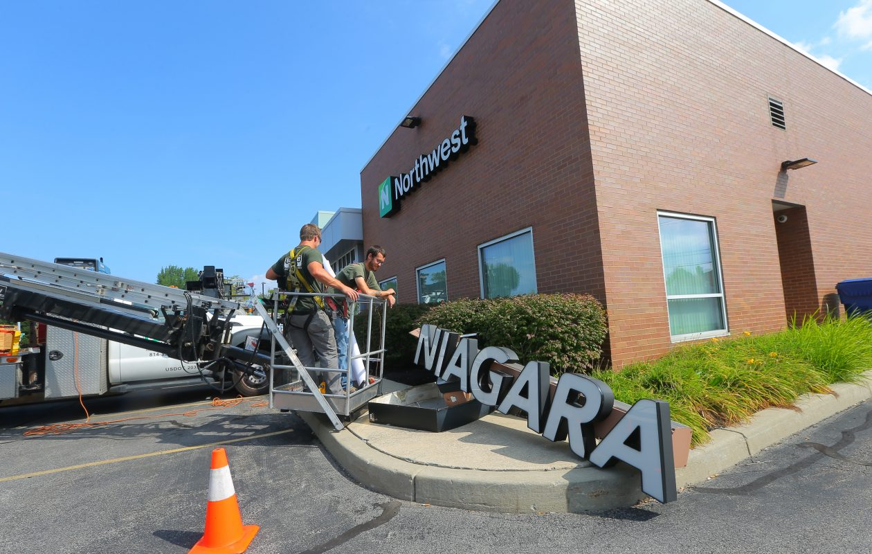 Northwest Bank's growth included the purchase of 18 former First Niagara Branch. Here, workers install a Northwest sign in 2016 after acquiring the branch.  (John Hickey/Buffalo News file photo)
