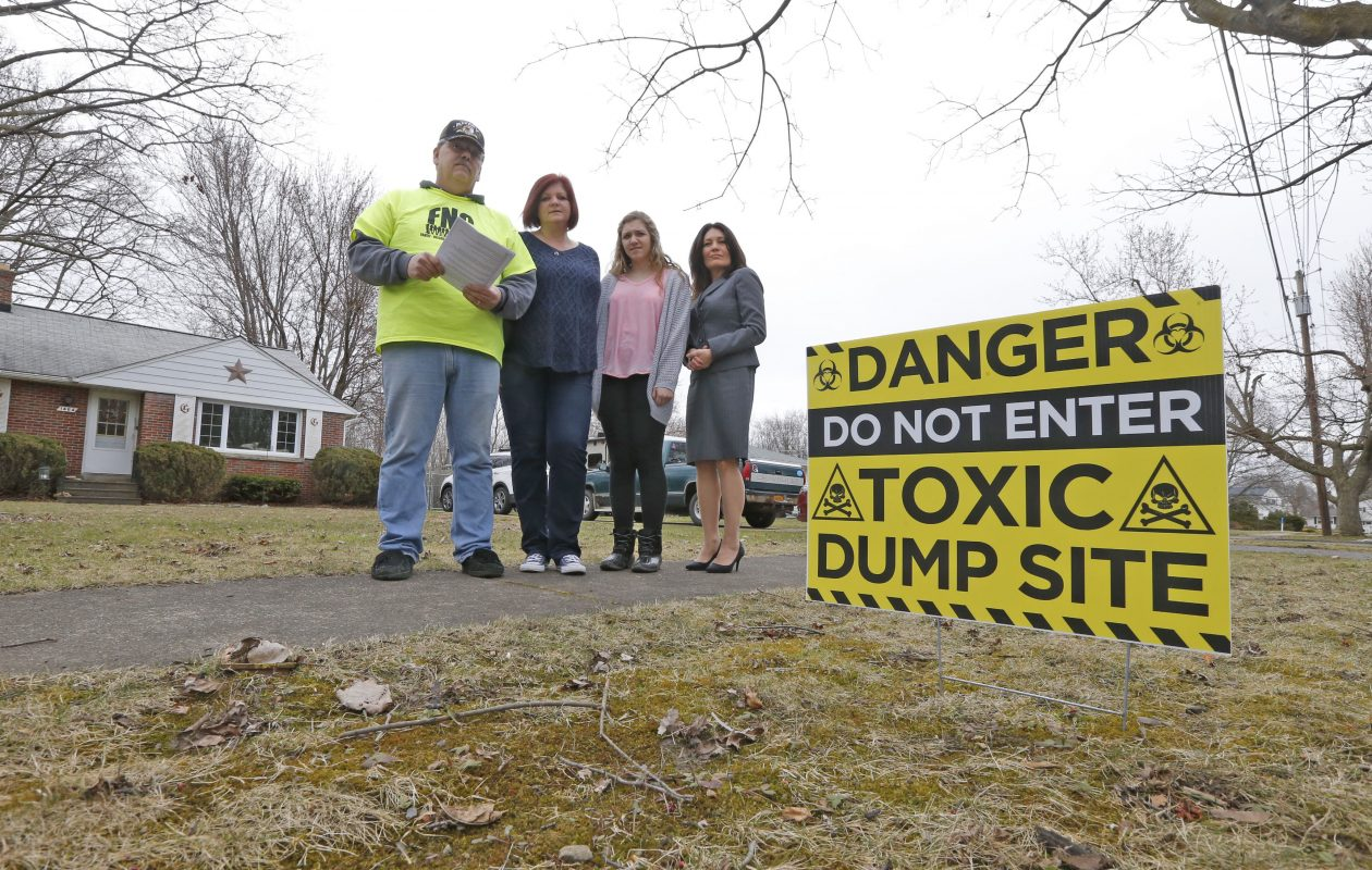 In this file photo, next to a sign on the Grawe Family's lawn in North Tonawanda, are from left, Brett, wife Becky and daughter Samantha with environmental attorney Christen Civiletto. Photo was taken on March 28, 2017. (Robert Kirkham/Buffalo News)