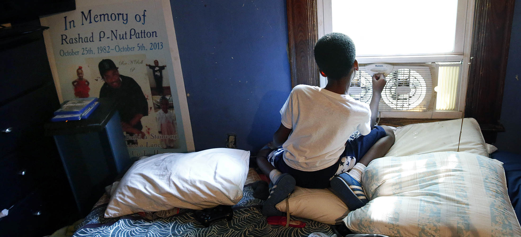 Jayden Lawson, now 9, lost his father to violence in 2013. At Jayden's left is a poster from his father's memorial service. It used to be a comfort to him, but on this day, he told his grandmother that he doesn't want it in his room anymore. (Sharon Cantillon/Buffalo News)