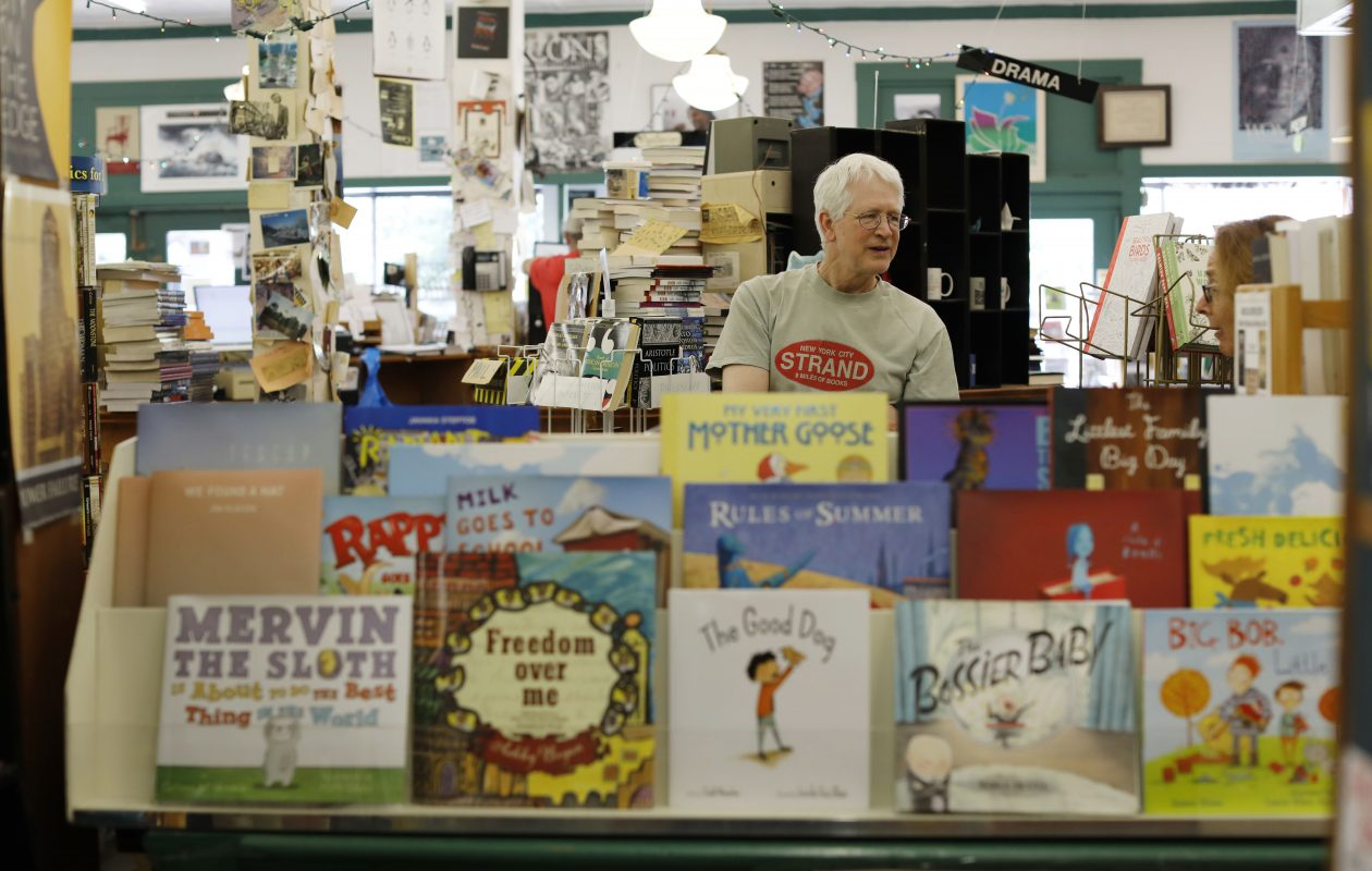 Jonathon Welch, owner of Talking Leaves Books, mingles with a customer at his Main Street store, which is closing as Welch consolidates his operations into his Elmwood Avenue location. (Derek Gee/Buffalo News)