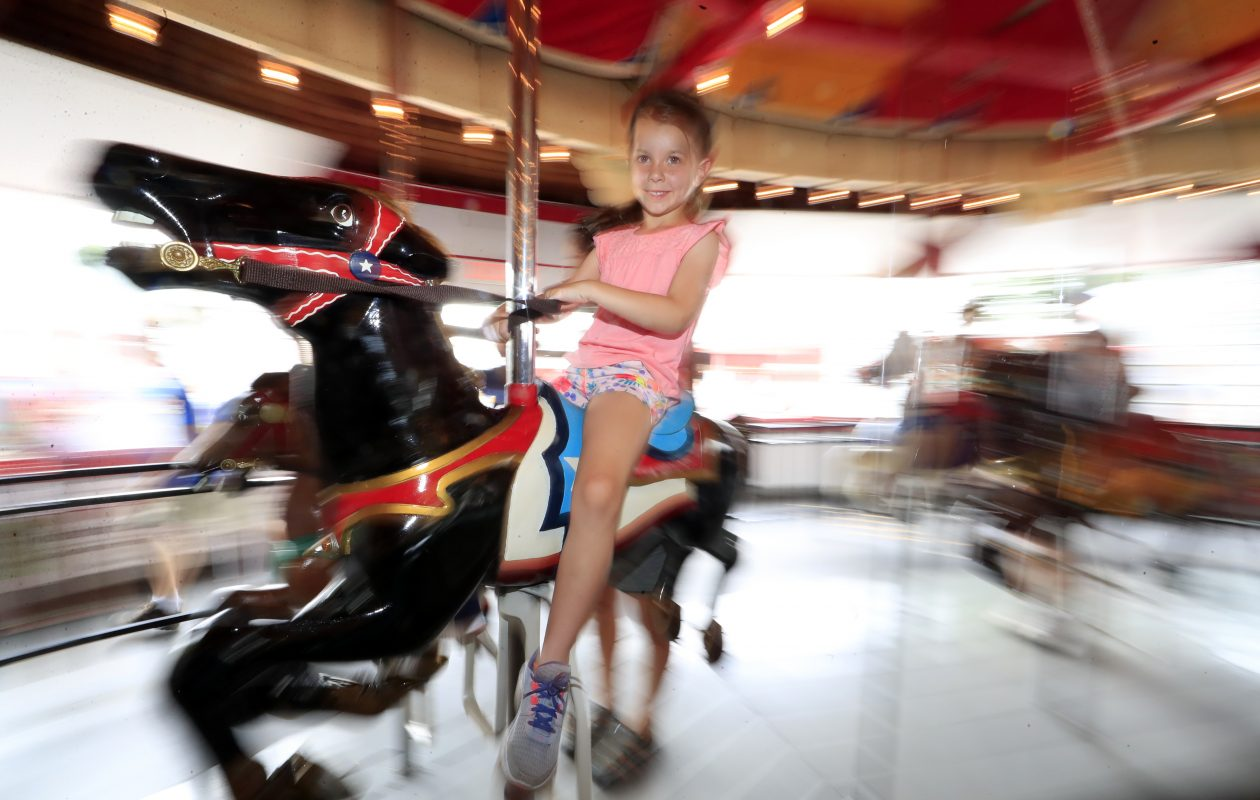 Brenna Lacki, 5, takes a spin on the fully restored 1928 Herschell-Spillman carousel that is the centerpiece of the Olcott Beach Carousel Park.  (Harry Scull Jr./Buffalo News)