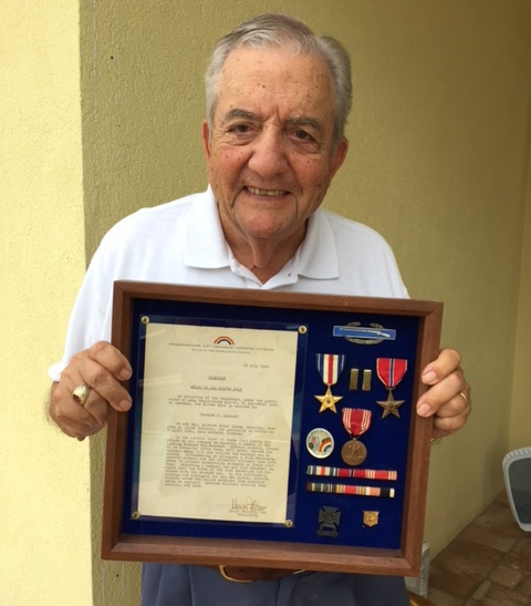 Charles Palmeri holds medals he earned in World War II.  (Provided photo)