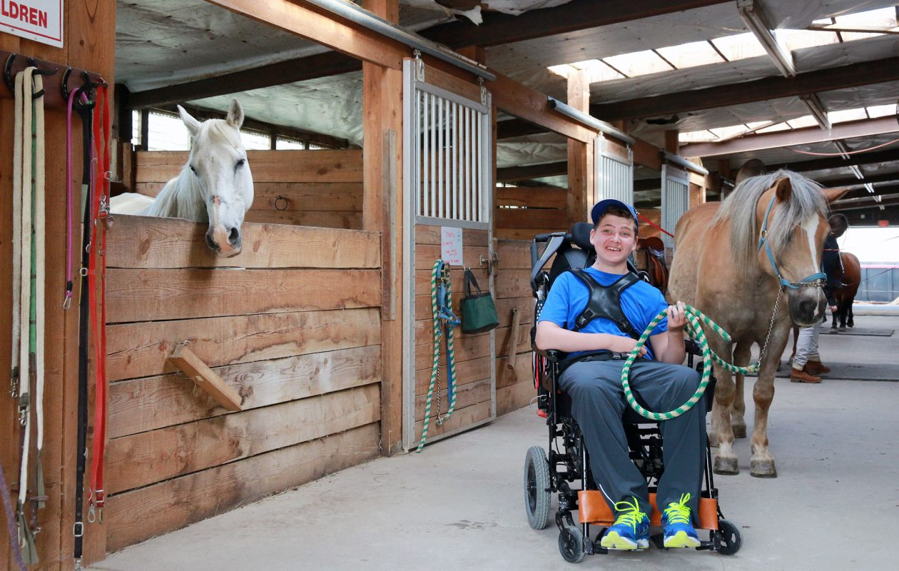 Matthew Evans enjoys spending time with the horses at Lothlorien Therapeutic Riding Center in East Aurora. (Dave Jarosz)