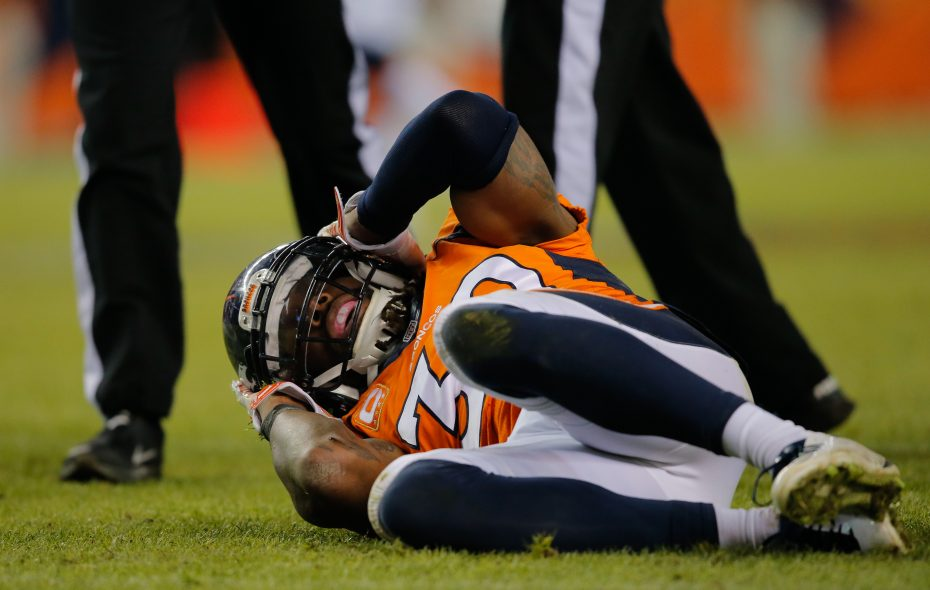 Broncos strong safety David Bruton lies on the ground in pain after a play that would force him out of the game with a reported concussion during a game against the Oakland Raiders in 2014. (Getty Images)
