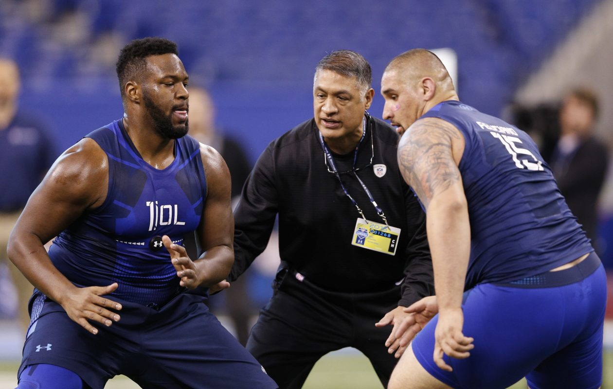 Offensive linemen Al Bond of Memphis and Jon Feliciano of Miami participate in a blocking drill for Baltimore Ravens line coach Juan Castillo during the 2015 NFL Scouting Combine at Lucas Oil Stadium on February 20, 2015, in Indianapolis. (Getty Images)