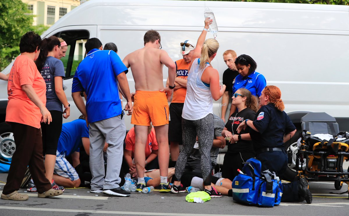 Medical personnel work on a fallen runner in Friday's Subaru 4 Mile Chase. (Harry Scull Jr./Buffalo News)