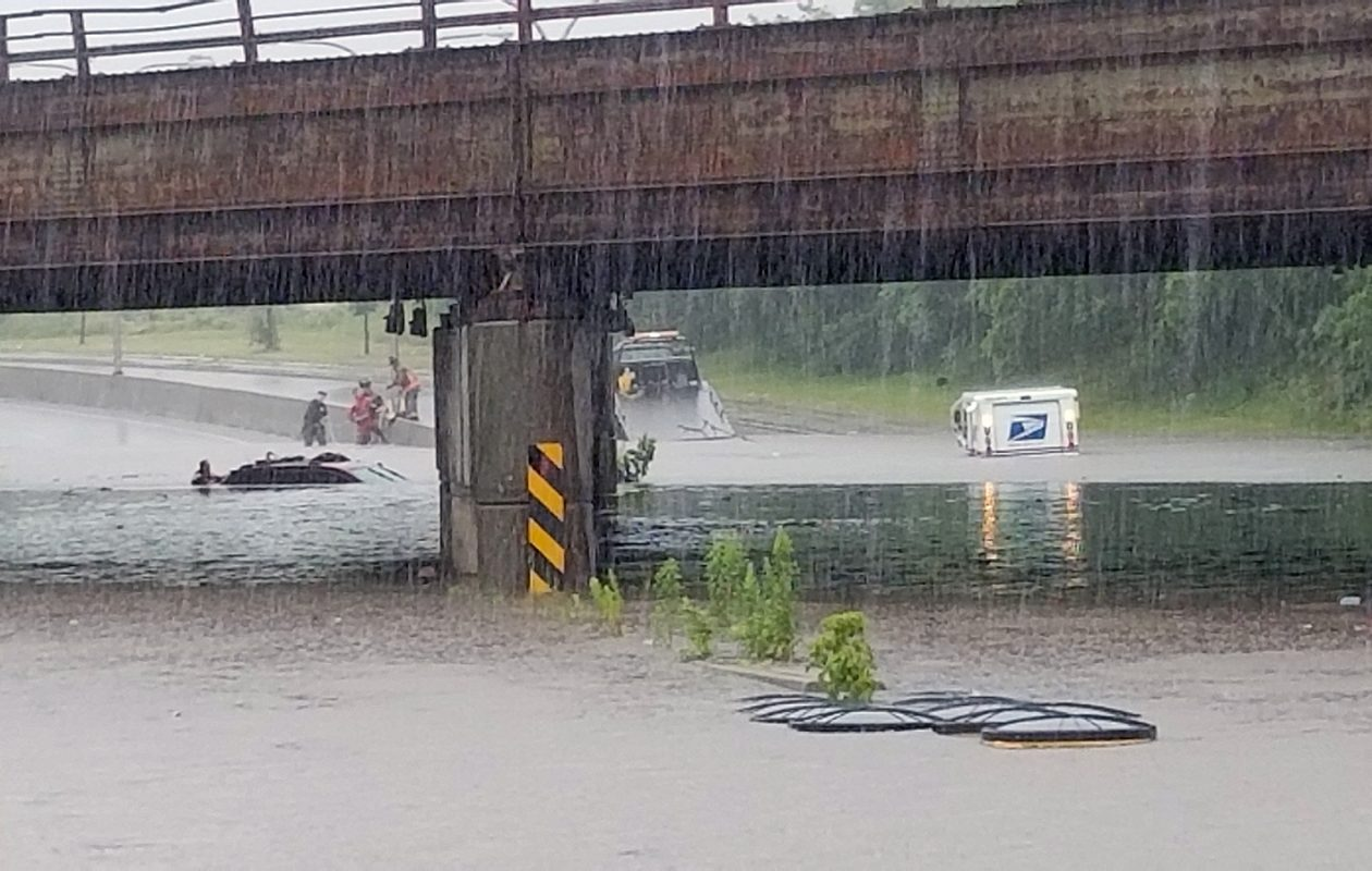 A mail truck (right) got stuck in the floodwaters Thursday during record-breaking rainfall. Three people were rescued from the vehicle on the left by Buffalo police and fire swift water rescue teams from this viaduct. (David F. Kazmierczak/Special to The News)