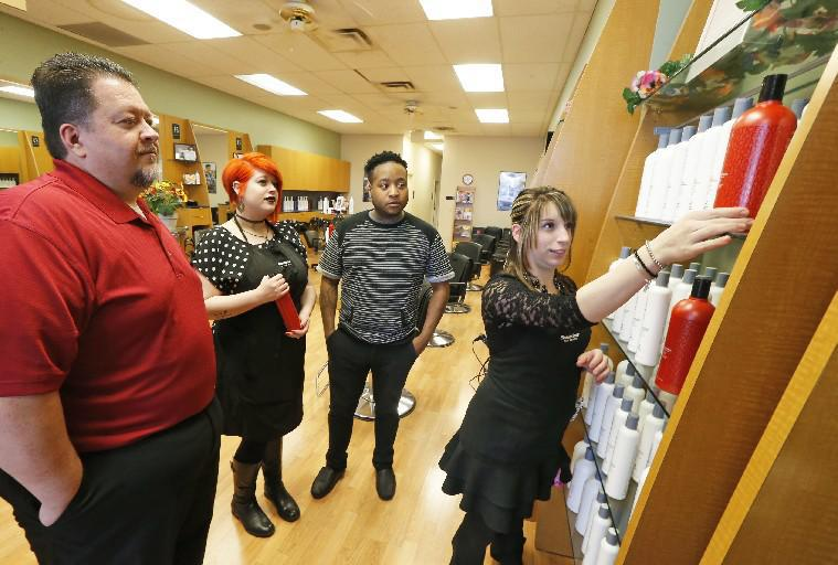 Michael Baer, left, has accepted a buyout of his lease to move his Fantastic Sams hair salon from the Northtown Plaza in Amherst. Here he discusses a new product line with some of his staff Sarah Meyers, Antonio Whitsett and Kristin Kolb back in April at the store, which is moving to 1330 Niagara Falls Blvd.  (Robert Kirkham/Buffalo News)