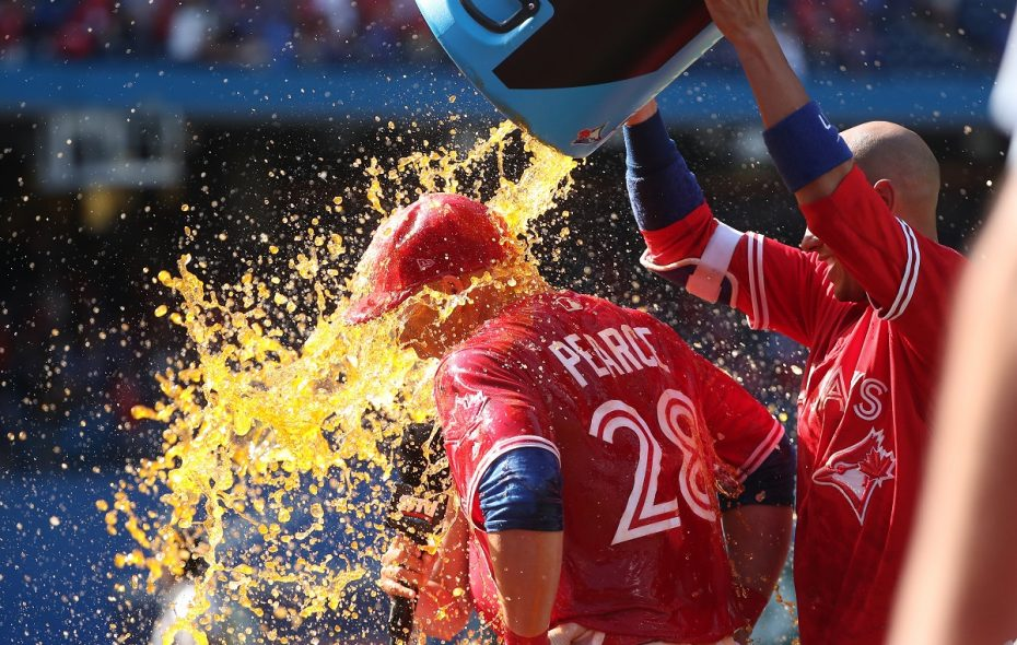 The Blue Jays' Steve Pearce receives the victory shower from teammate Ryan Goins after becoming just the third player in Major League history to hit two walk-off grand slams in the same season during an eventful sports Sunday. (Photo by Tom Szczerbowski/Getty Images)