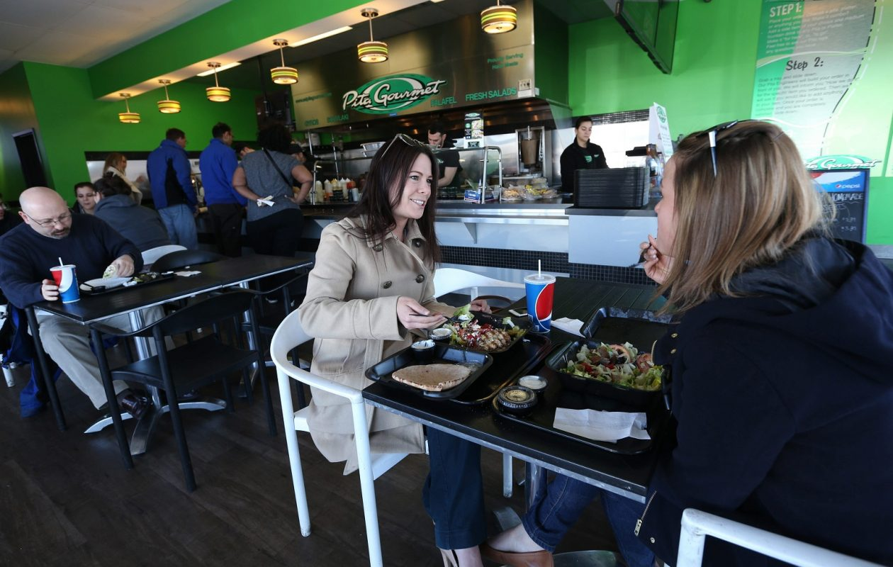 In this file photo from March 24, 2015, co-workers Cori Sannicola and Sarah Morein enjoy a lunch of authentic Greek and Mediterranean cuisine at the Pita Gourmet at 6733 Transit Road in Lancaster. The company plans to open a new location up Transit Road in Clarence in a new Bevilacqua Development building. (Sharon Cantillon/Buffalo News file photo)