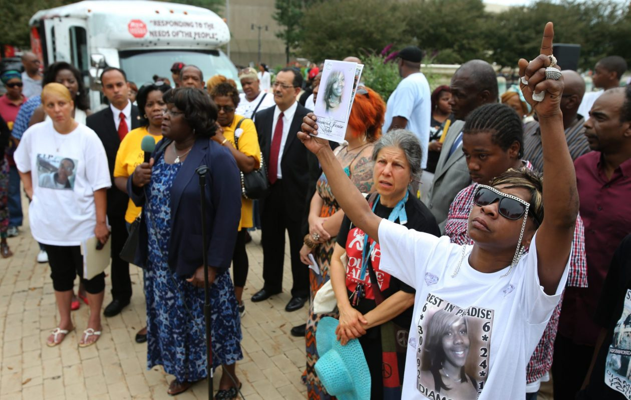 Cathy Toler, right, of Buffalo, holds a photo of her slain daughter, Diamond Toler, at a 2013  Stop the Violence rally in Niagara Square. (News file photo)