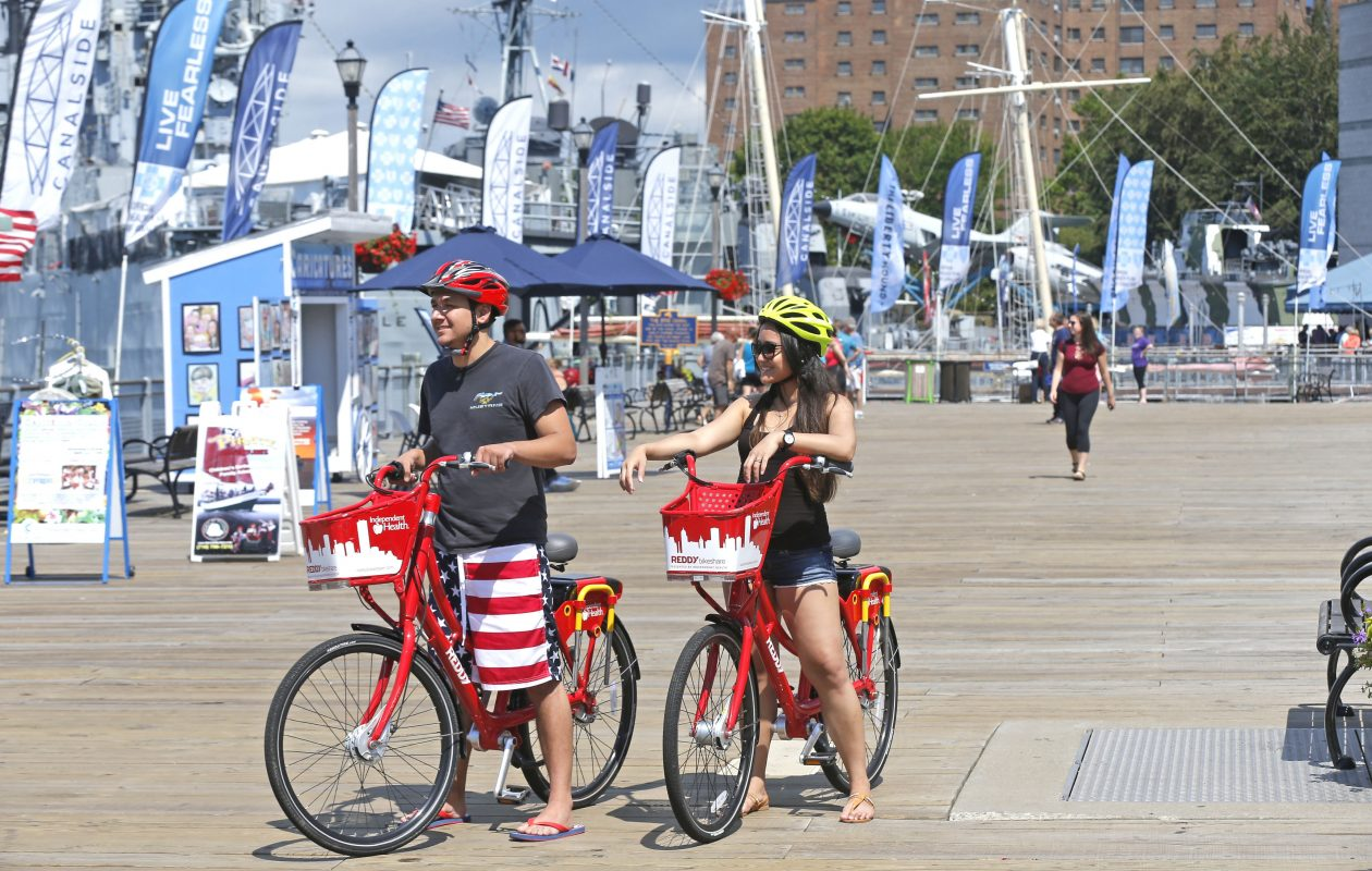 Austin Bobeck, left, of Cheektowaga, and his girlfriend, Mabel Integro, of West Seneca, explore Canalside on their rented Reddy Bikes. (Robert Kirkham/News file photo)