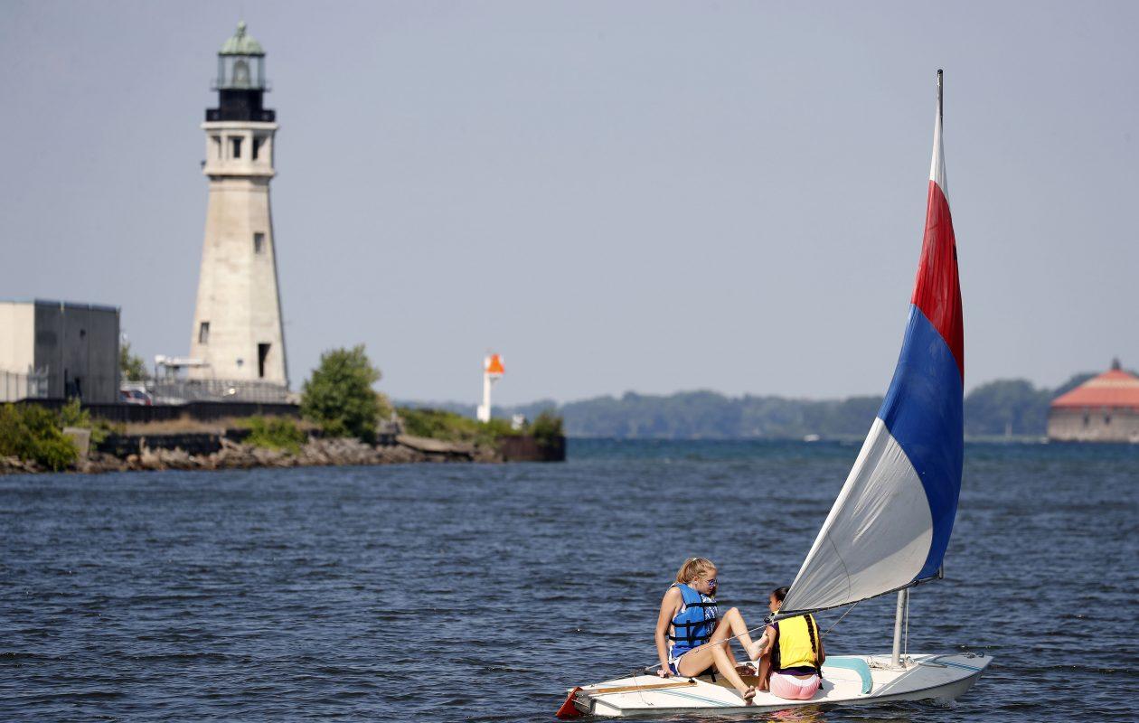 Brooke Willer, left, and Kasandra Castro, right, sail past the historic lighthouse in Buffalo's harbor on Monday, July 31, 2017. (Mark Mulville/Buffalo News)
