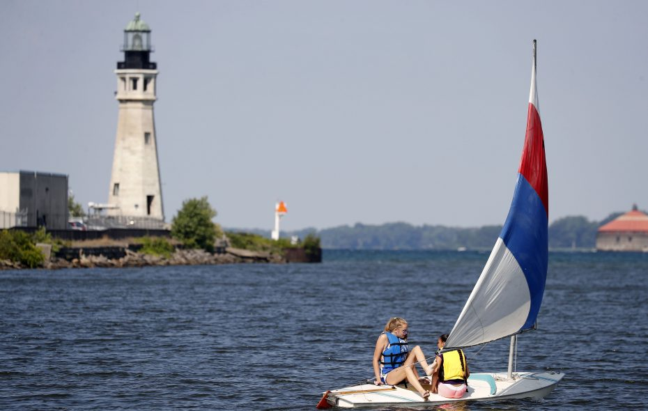 Brooke Willer, left, and Kasandra Castro, right, sail past the historic lighthouse in Buffalo's harbor on Monday, July 31, 2017. (Mark Mulville/Buffalo News)