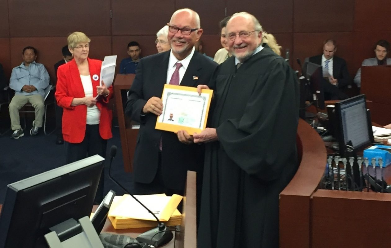J.P. Bak holds his citizenship certificate with Judge Michael Kaplan, who presided over the ceremony.