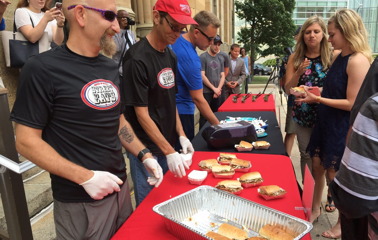Michael Pierro III, left, and James Giannicchi, who run the Mineo & Sapio Street Eats food truck, pass out samples Friday at City Hall of their Dirty Bird reduced sodium chicken Italian sausage sandwiches, to help whet the appetites of healthy eaters who will visit the Taste of Buffalo this weekend. (Photos by Scott Scanlon/Buffalo News)