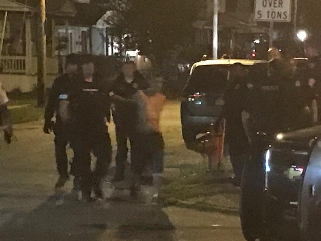 Police escort the man who threatened to blow up his Thomas Street house Wednesday night. (Photo provided)