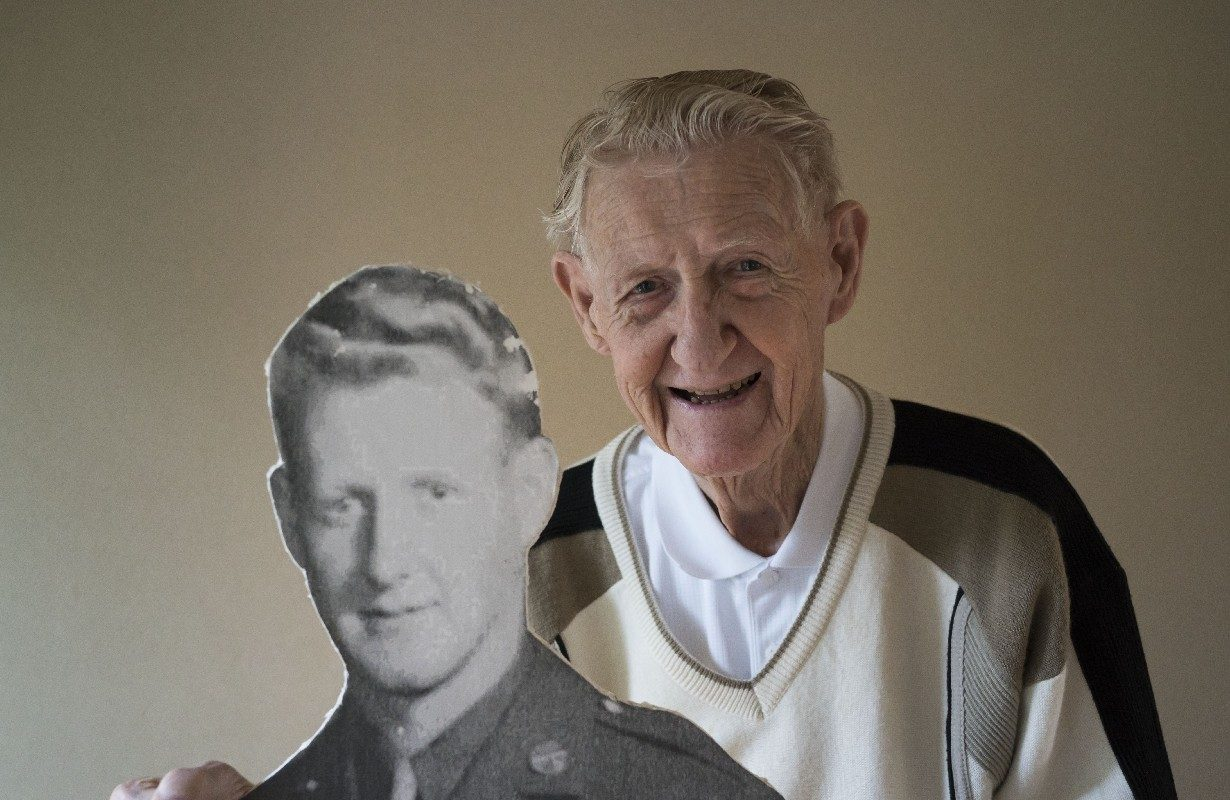 World War II paratrooper James May poses with a cutout of himself made by his children for a recent birthday. (Derek Gee/Buffalo News)