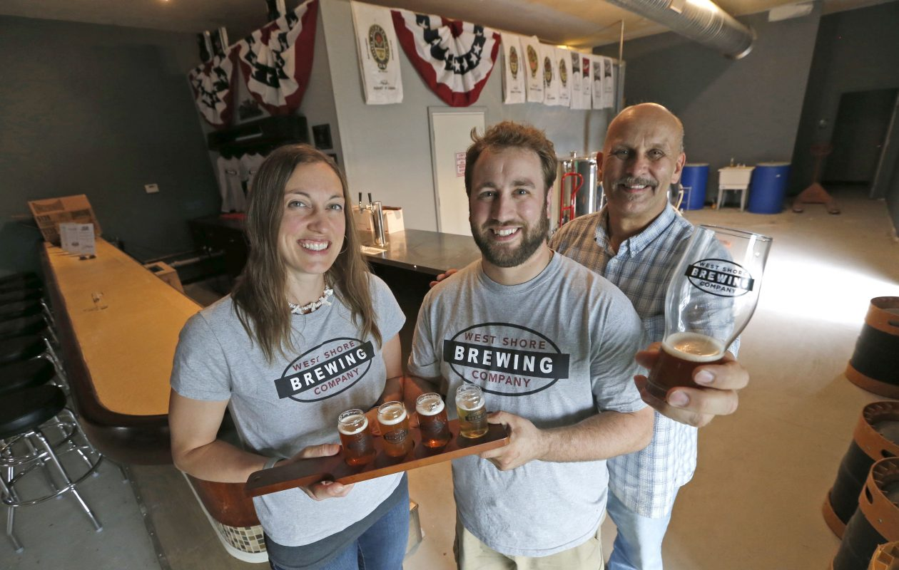 West Shore Brewing Company owners, from left, Laura, Josh and Greg Dziomba, have opened the first brewery in Clarence, at 10995 Main St., next door to Antique World & Flea Market.  They plan to add a beer garden later this spring. (Robert Kirkham/Buffalo News)