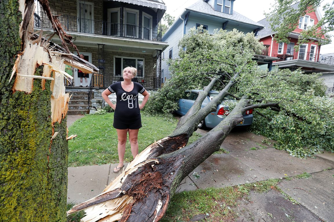 Kendra Dunkleman stands near her car that was crushed by a tree during Friday afternoon's storm.  She had just safely gotten out of the car and into the house in South Buffalo when the tree was struck by lightning.            (Mark Mulville/Buffalo News)
