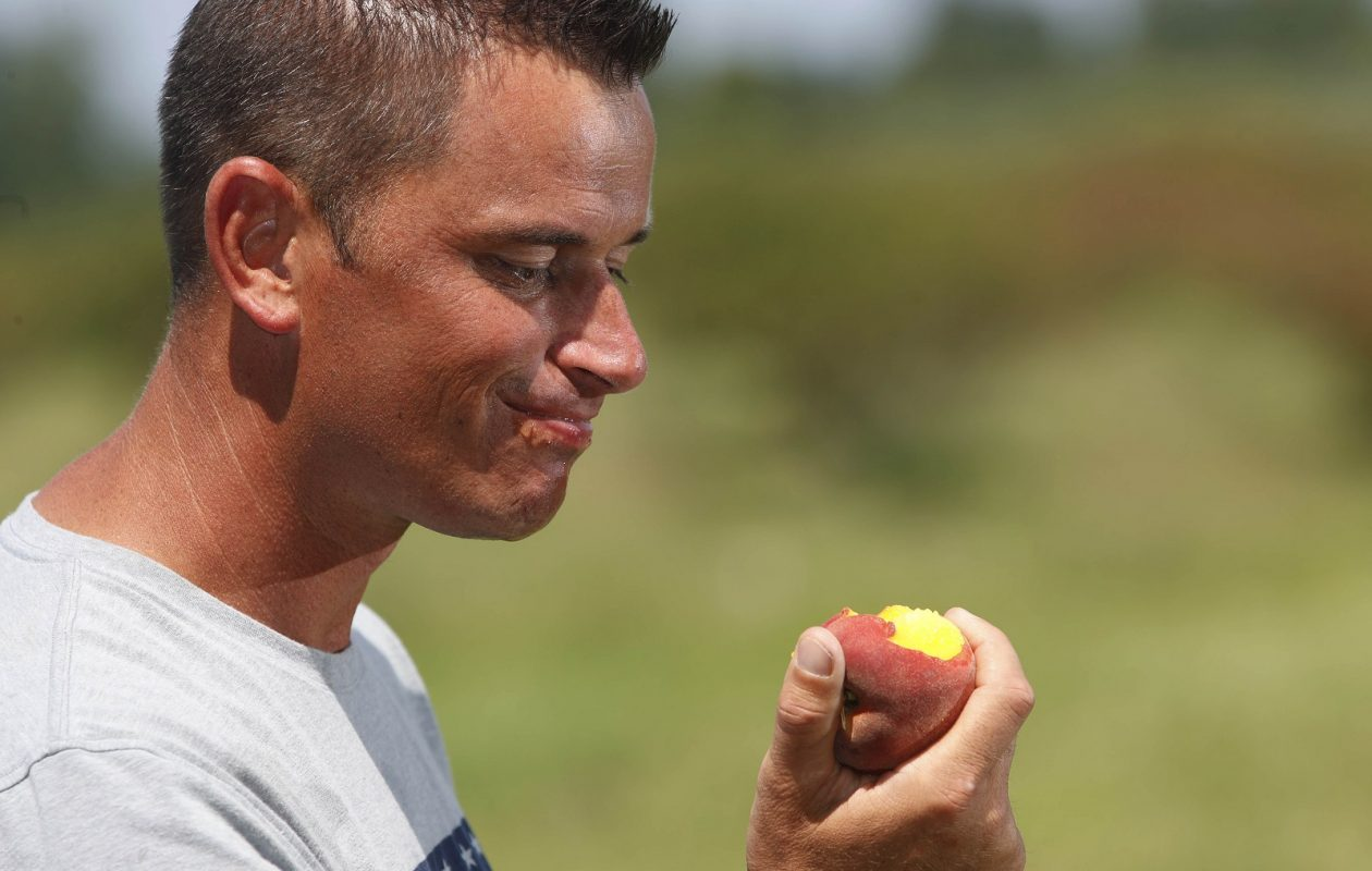 Kevin Fildes, the owner's son-in-law, bites into a refreshing peach on a hot afternoon. (Sharon Cantillon/Buffalo News)