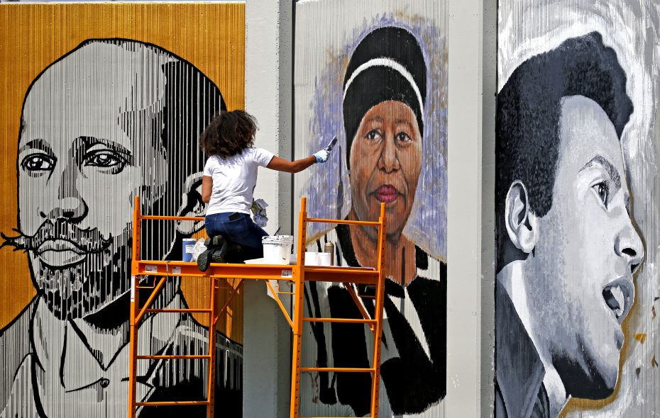 """Artist Julia Bottoms-Douglas paints a portrait of Eva Doyle. on """"The Freedom Wall, an ambitious public art project featuring portraits of local and national civil rights leaders. (Robert Kirkham/Buffalo News)"""