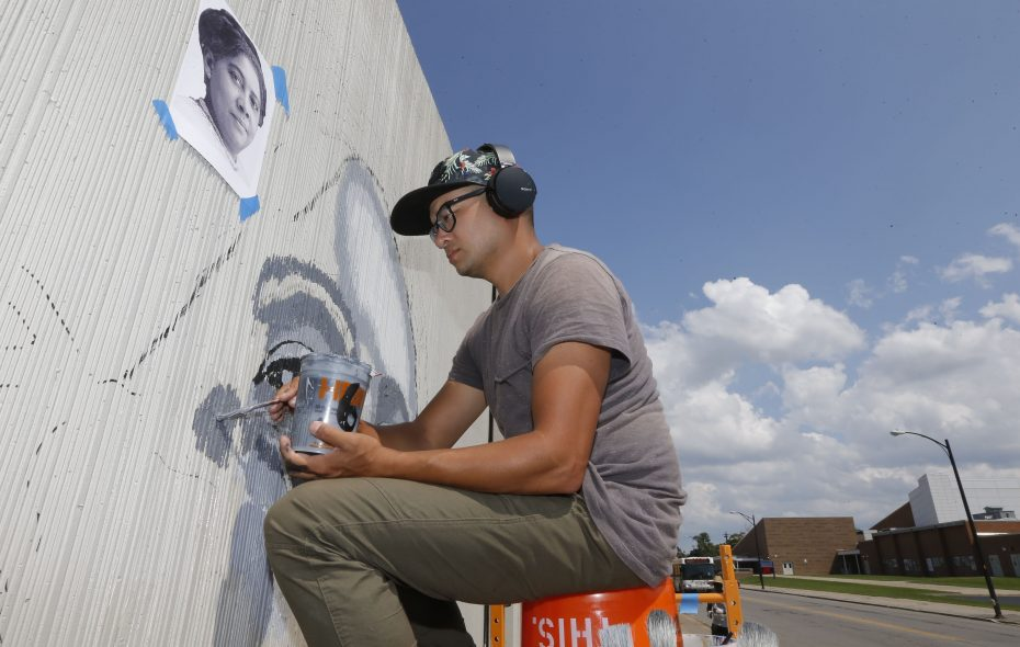 """Artist Chuck Tingley paints a portrait of Mary B. Talbert on """"The Freedom Wall,"""" an ambitious public art project featuring portraits of local and national civil rights leaders on East Ferry Street. (Robert Kirkham/Buffalo News)"""