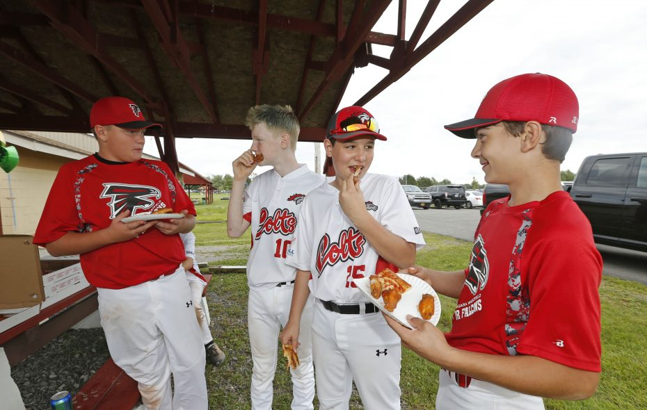 Niagara Wheatfield Falcons players dressed in red, Wyatt Cooper, left, and Joey Haynes, wait for reaction as players from the Australian Colts team, Ty Spaulding from Perth and Caleb Garren from Canberra, sample chicken wings between games at Fairmont Park in Wheatfield. (Robert Kirkham/Buffalo News)