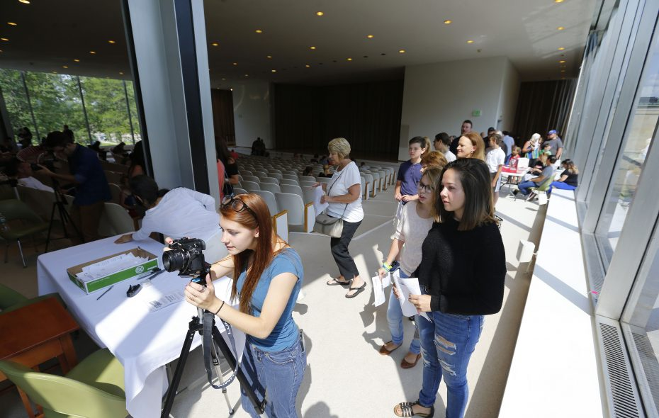 """Mandy Hebblethwaite snaps photos of those standing in line for a casting call for the newest feature film to be made in the area, """"Adventures of Wolfboy"""", at the Albright-Knox Art Gallery in Buffalo on Aug. 26. (Mark Mulville/Buffalo News)"""