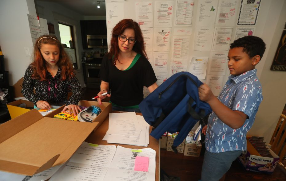 Deanna Farina, center,  and her daughter Abigail Gray, 9, left, and Dylan Carpenter, 10, right,  of the company, Abba Doo & Dylan Too, package some supply packages for back-to-school shopping. (John Hickey/Buffalo News)