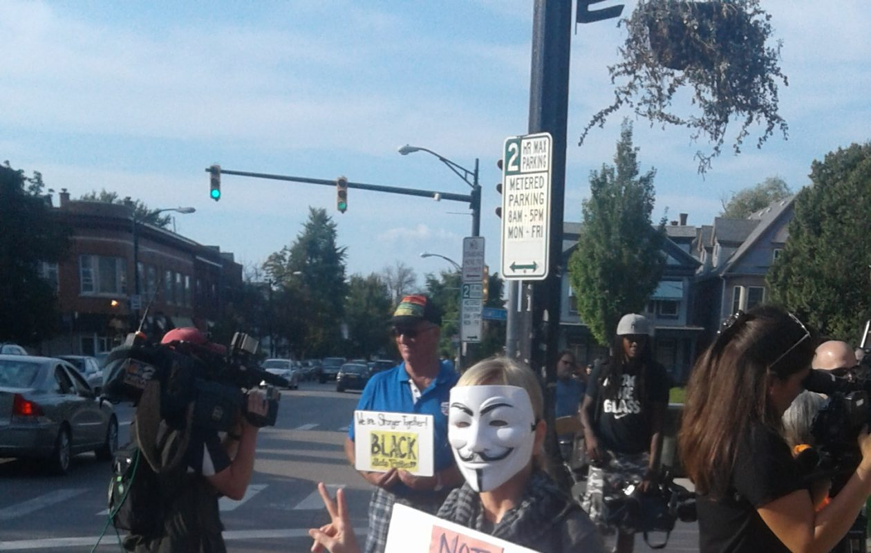 A woman wearing an Anonymous facemask greets drivers at a rally at Elmwood Avenue and Bidwell Parkway Aug. 13, 2017. (Thomas J. Prohaska/The Buffalo News)