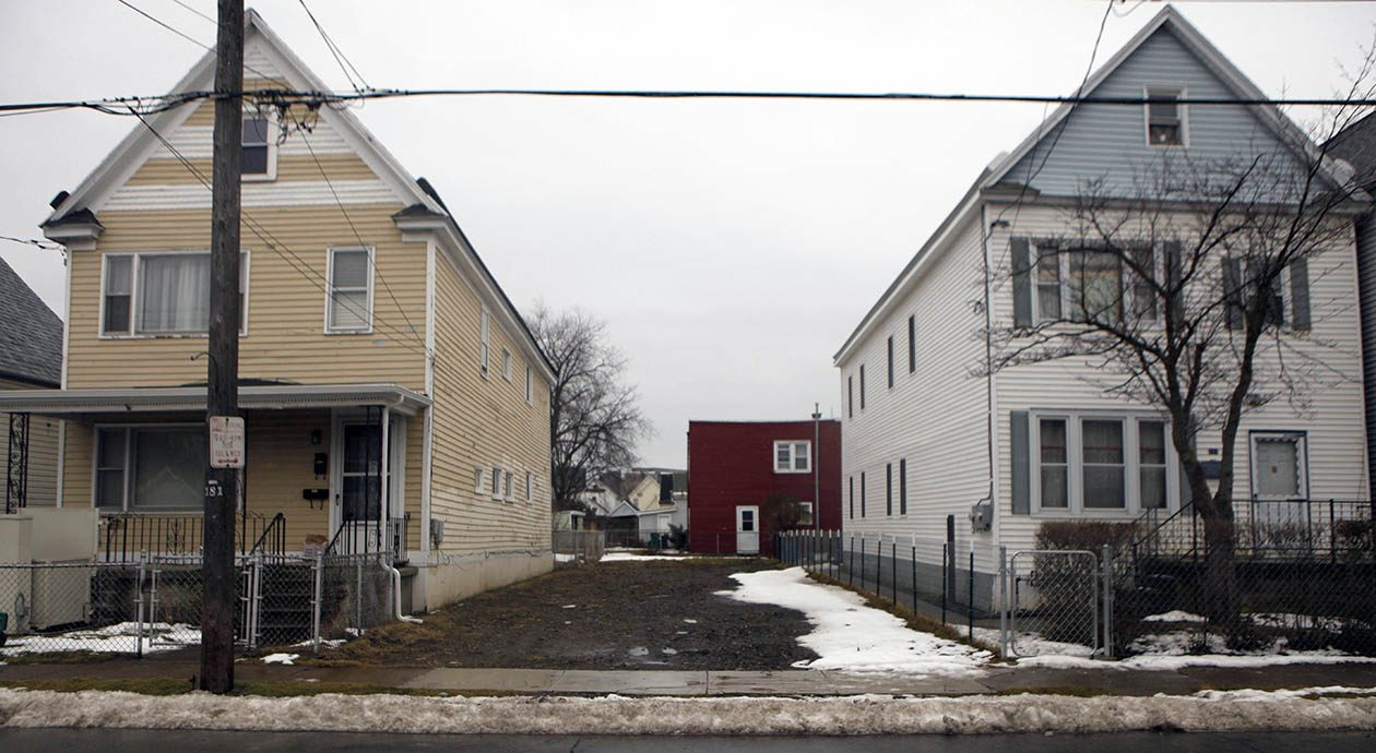 An empty lot is all that remains at 179 Mackinaw Street in Buffalo's Old First Ward, after an arson fire displaced the residents there, who were immigrants from Congo, Thursday, Feb. 16, 2012.   (Photo by Derek Gee / Buffalo News}