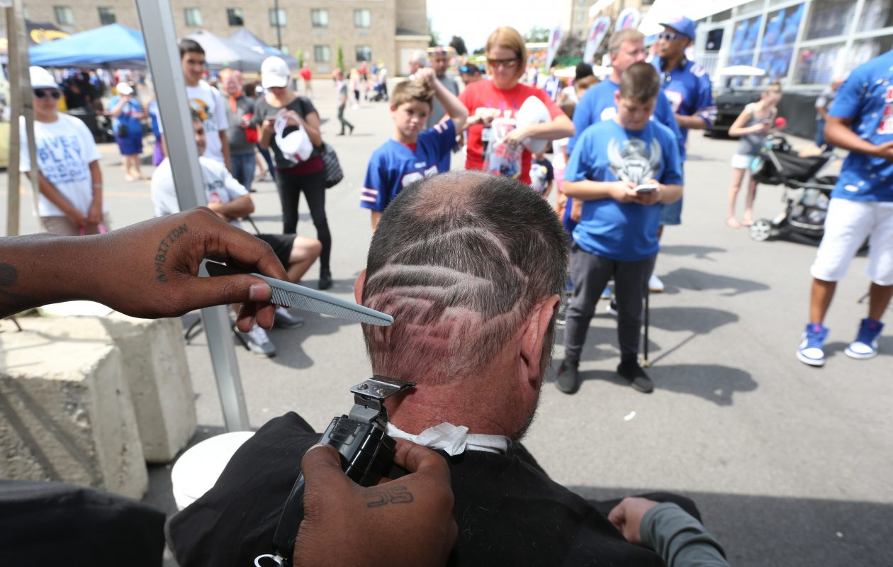Signature Cutz barber Charles 'Ronnie' Burley cuts a Bills logo into the hair of Dan Mealy of Jamestown at the barbershop's tent at the Bills' training camp at St. John Fisher College in Pittsford, N.Y. on Sunday, Aug. 6, 2017. Signature Cutz, which calls itself the unofficial barbershop of the Bills, cuts the hair of many of the players. At the training camp, it offers fans free haircuts every Sunday.  (James P. McCoy / Buffalo News)