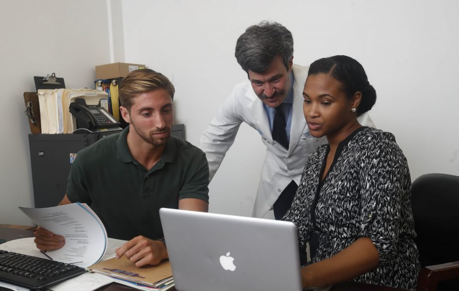 Nicholas Bossert, left, a fourth-year physician assistant student at Daemen College, and Narissa Williams, who is  about to start medical school at the University at Buffalo, spent the summer doing research at the DART Methadone Clinic on Main Street in Buffalo. They flank Dr. Andrew Talal, a UB professor and attending physician at Buffalo General Medical Center, who leads the research. (Sharon Cantillon/Buffalo News)